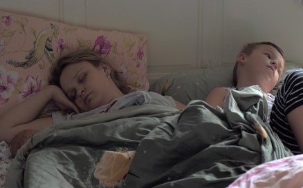 Sleeping mom, baby and elder son in bed people Stock Video