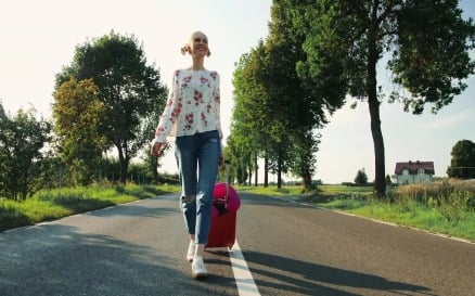 Cheerful Young woman with suitcase walking on road - video footage Stock Video
