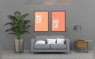 A Comfortable Gray Sofa With White Cushions In A Room With Frames On A Wall Product Mockup